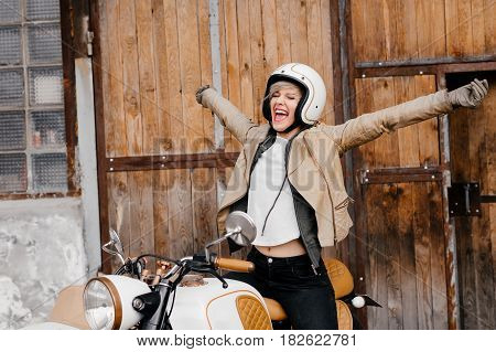 Smiling girl on a motorcycle. Happy girl shows direction. Motorcycle kaferacers. White and brown motorcycle with a large sidecar. The girl shouts happily