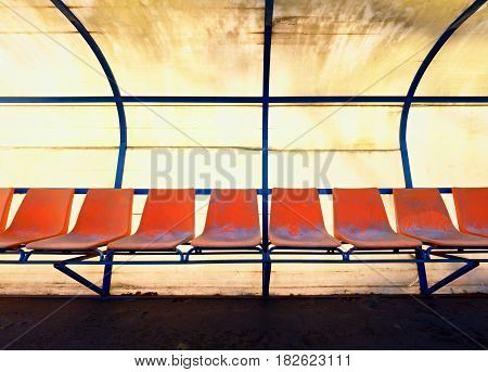 Vintage Plastic Seats On Outdoor Stadium Players Bench, Chairs With Worn Paint Below Yellow Roof.