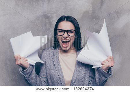 Portrait Of Frustrsted Girl Which Crumples Papers On A Grey Backgroung