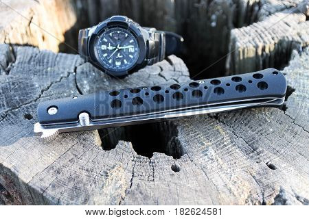 Knife Is Fold And Watch. Wooden Stump.