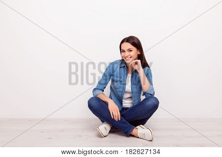 Nice-looking Young Cheerful Girl Touching Her Chin And Sitting On The Floor With Crossed Legs Agains