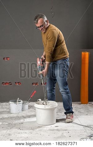 Adult worker mixing paint with mixer.