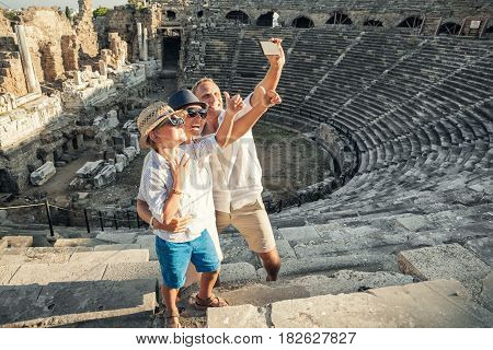 Young positive family take a self photo on the antique amphitheater in Side Turkey