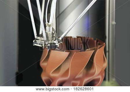 Modern 3D printer printing figure close-up macro. Automatic three dimensional 3d printer performs plastic brown colors modeling in laboratory.