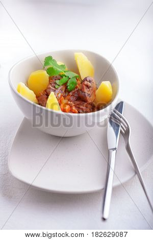 Beef stew being in a slow cooker, garnished with potatoes and champignons