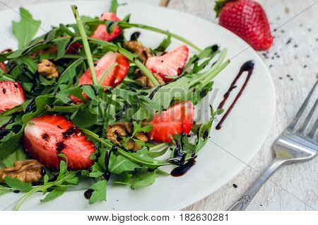 Fresh salad with arugula strawberries nuts black sesame seeds and balsamic glasse sauce served on white plate on rustic wooden table. Healthy organic diet food concept. Selective focus.