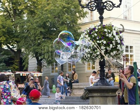Lvov, Ukraine - August 18, 2016: Man inflates big soap bubbles on Market Square. Wiev of city life