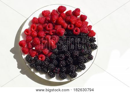 Fresh raspberries and blackberries on plate lined with symbol of yin and yang isolated on white background top view