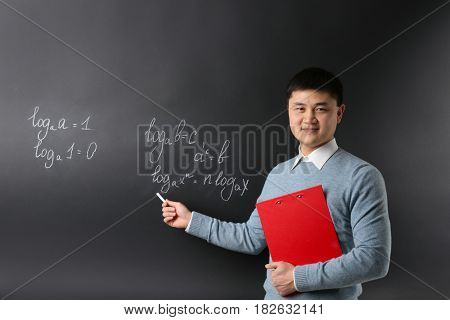 Handsome young Asian teacher with clipboard on blackboard background