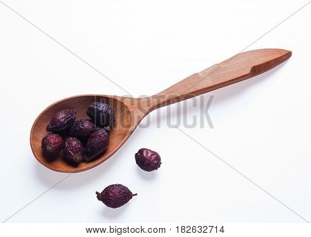 Dry berry Rose hips in wooden spoon isolated on white background
