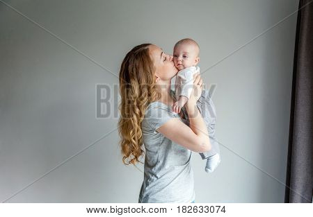 Young mother holding her newborn child. Woman and new born boy relax in a white bedroom. Mother breast feeding baby. Family at home. Young mother playing whith her newborn son