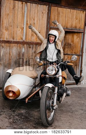 Smiling girl on a motorcycle. Happy girl shows emotions. Motorcycle kaferacers. White motorcycle with a large sidecar. The girl shouts happily. Wow