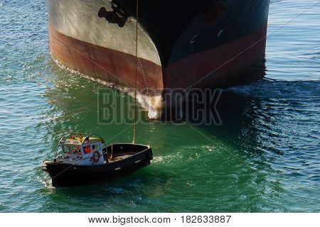 Big container ship in port with small boat in front. Huge cargo boat black and red follow mooring service boat. Vessel in habour Barcelona. Transport service on calm sea water shipping slowly. Transport for business. Ships working. Travel by sea.