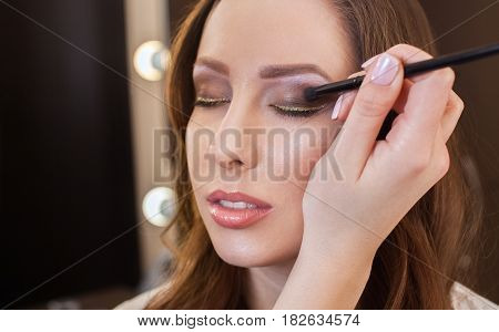 The make-up artist paints eyes with eye shadow in the beauty salon.