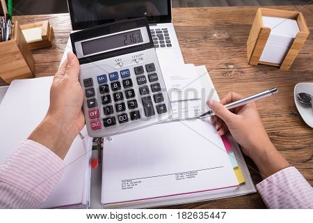 Businesswoman Holding Calculator In Her Hand Calculating Invoice On Desk