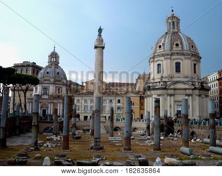 Ancient ruins of the Trajan's forum in Rome Italy. Imperial forum traiani and Santa Maria di Loreto Church. Ancient roman ruins with Trajan's column under blue sky.