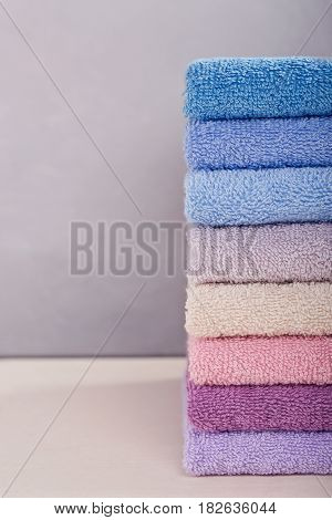 High stack of colorful bath towels on light background. Pastel colors cotton or bamboo towels. Hygiene fabricspa and textile concept