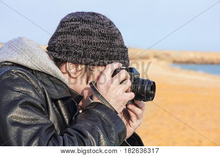 Photographer using retro photo camera on sea beach.