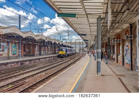 Ipswich, UK. 17th April 2017. A class 360 Desiro EMU is about to depart for London in the distance. Some people remain on the platform awaiting a connection.