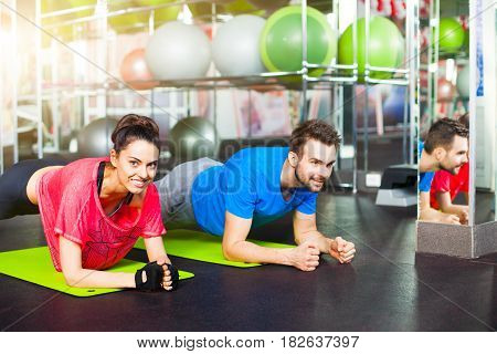 Sport - young fitness couple in  gym. Sport couple doing pushups bar on floor in the gym.