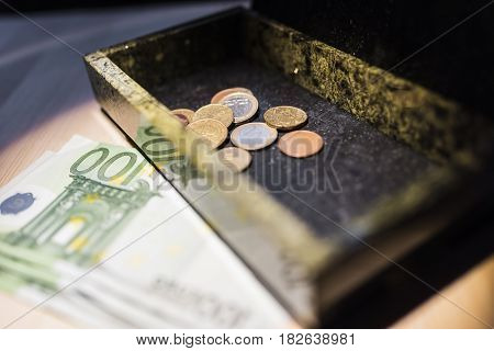 Paper money bills of one hundred euros on the table and a few euro coins in a green malachite box. Financial stability concepts.