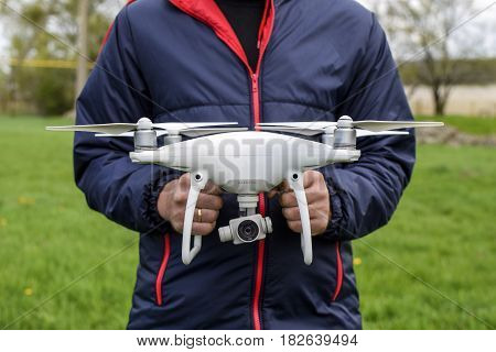 A Man With A Quadrocopter In His Hands. A White Drone Is Being P