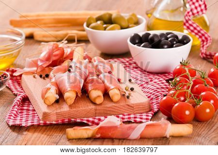 Grissini breadsticks with ham and olives on cuttingboard.