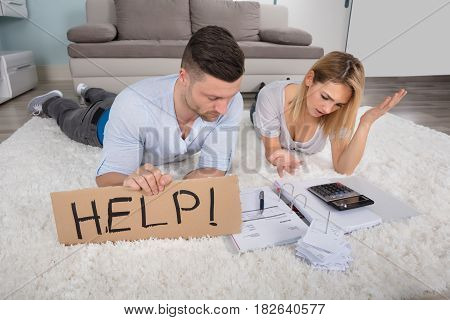 Frustrated Couple Holding Help Sign While Calculating The Bills At Home
