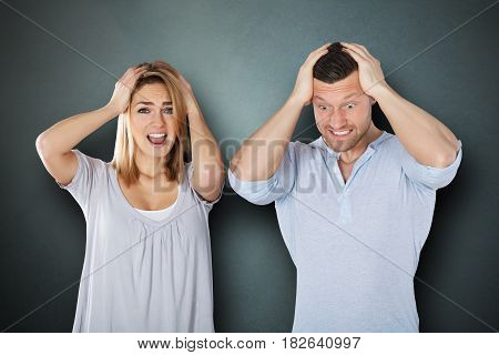 Portrait Of A Young Frustrated Couple Against Grey Background
