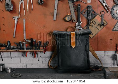 Exclusive black leather backpack. Backpack near the wall. The tools in the garage. Many different tools