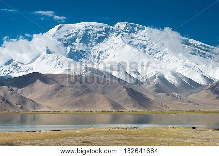 Xinjiang, China - May 21 2015: Mustagh Ata Mountain At Karakul Lake. A Famous Landscape On The Karak