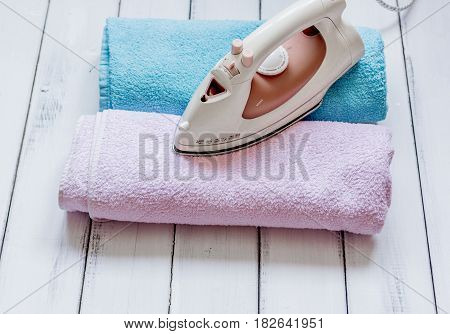 ironing pile of colorful towels in laundry housekeeping concept on light desk background