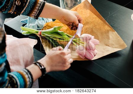 Small business. Male florist hands closeup, cuts rose for bouquet in flower shop. Man assistant or owner in floral design studio, making decorations and arrangements. Flowers delivery, creating order