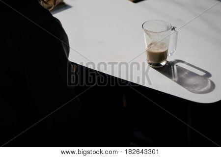 high-angle shot of a blank notepad, a pen and a cup of coffee on a white table