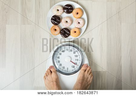 A Person's Feet On Weight Scale With Dish Of Donuts On Floor