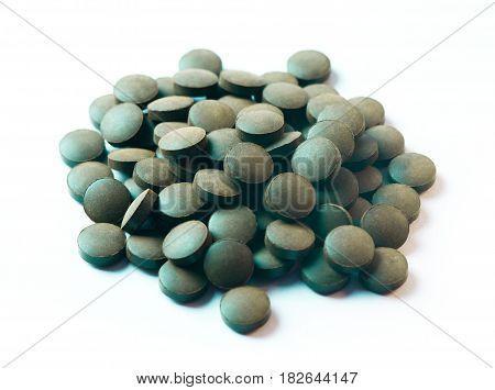 Round pills of Spirulina isolated on white background