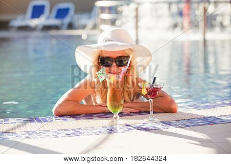 Blonde woman in hat at the swimming pool