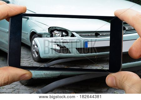 Close-up Of A Person's Hand Taking Photo Of Car Accident Through Smartphone