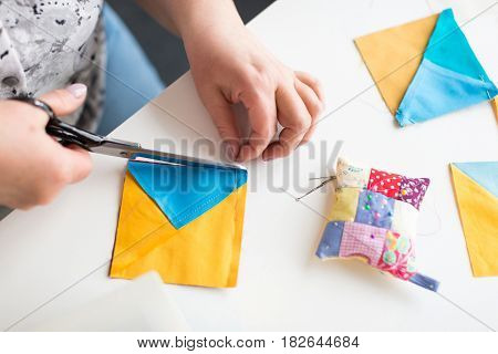 patchwork and quilting in the workshop of tailor woman - close-up on tailor scissors cuts the thread on the blue and yellow scraps of fabric for patchwork on the desktop with thread, pins and cushion