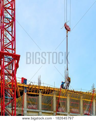 Crane and workers at construction of building against blue sky