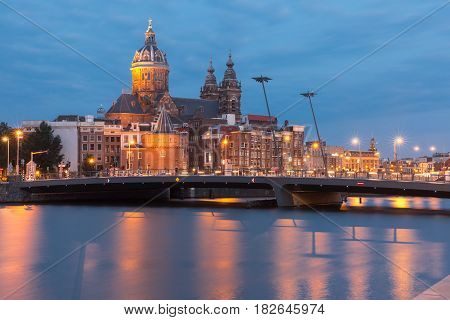 Night city view of Amsterdam canal, bridge and Basilica of Saint Nicholas, Holland, Netherlands. Long exposure