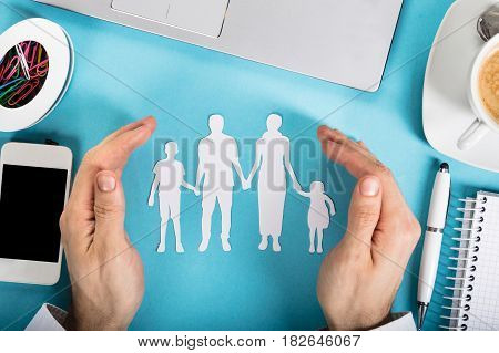 A Businessman's Hand Protecting The Paper Cut Out Family With Office Supplies On Office Desk