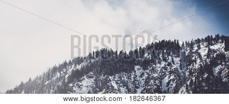 Panoramic view of a snow-capped alpine summit obscured by clinging white clouds viewed behind a forested ridge with fir trees