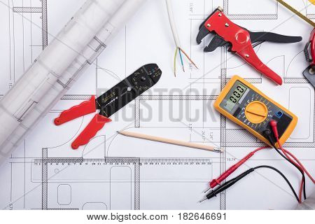 High Angle View Of Electrical Instrument With Tools And Digital Multimeter On A Blueprint