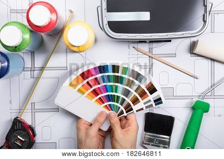 Elevated View Of An Architect Choosing Color From Swatch On Blueprints In Office