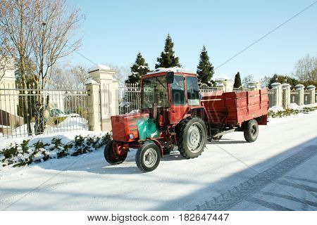 Winter road with tractor outside city