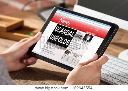 Close-up Of A Woman Reading Scandal News On Digital Tablet