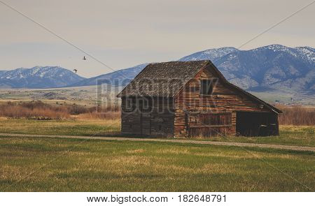 Landscape with a rustic vintage barn with. mountains in background.