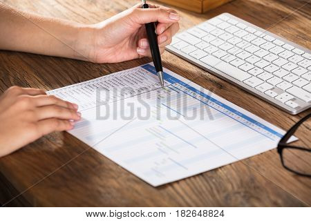 Close-up Of A Businessperson Analyzing The Gantt Chart On Wooden Desk