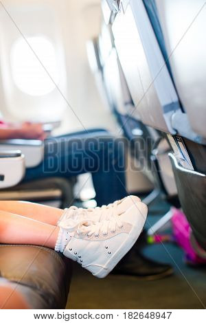 Baby feet on seat in the aircraft